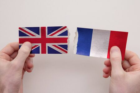 UK and France paper flags ripped apart. political relationship concept