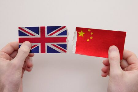UK and China paper flags ripped apart. political relationship concept