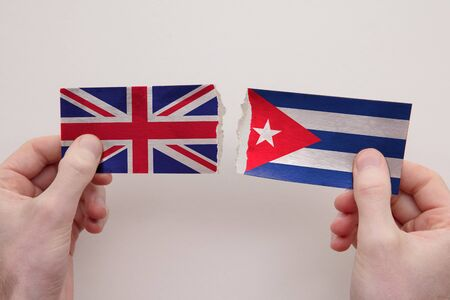 UK and Cuba paper flags ripped apart. political relationship concept