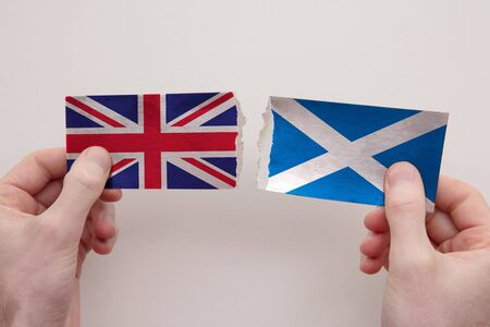 UK and Scotland paper flags ripped apart. political relationship concept