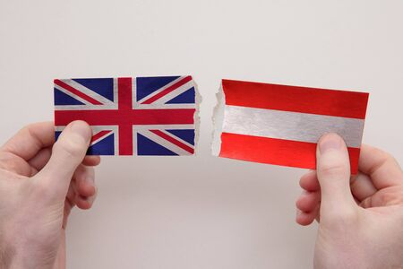 UK and austria paper flags ripped apart. political relationship concept