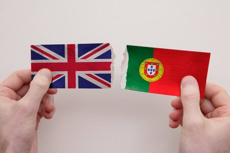 UK and Portugal paper flags ripped apart. political relationship concept