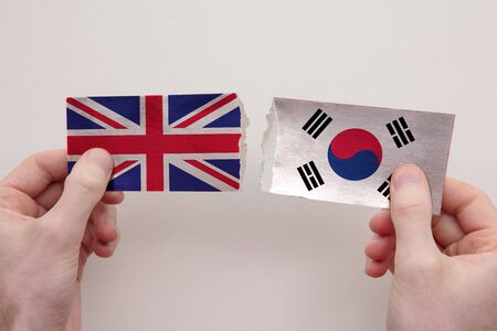 UK and South Korea paper flags ripped apart. political relationship concept