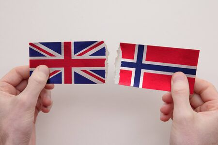 UK and Norway paper flags ripped apart. political relationship concept