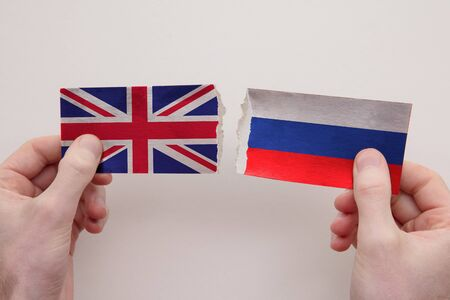 UK and Russia paper flags ripped apart. political relationship concept
