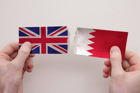 UK and Bahrain paper flags ripped apart. political relationship concept