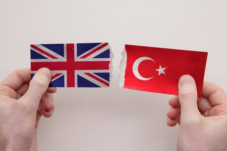 UK and Turkey paper flags ripped apart. political relationship concept