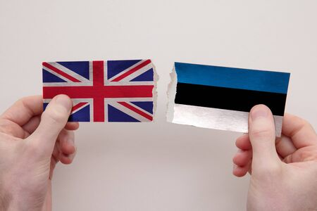 UK and Estonia paper flags ripped apart. political relationship concept