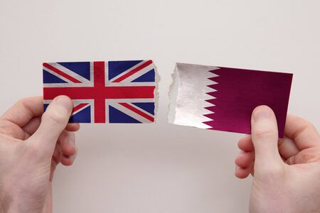 UK and Qatar paper flags ripped apart. political relationship concept Stock fotó