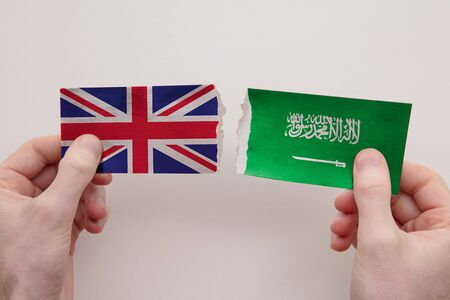 UK and Saudi Arabia paper flags ripped apart. political relationship concept