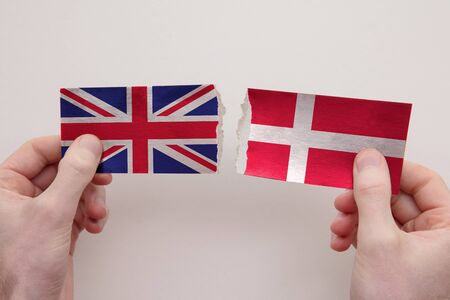 UK and Denmark paper flags ripped apart. political relationship concept 写真素材