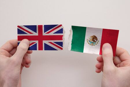 UK and Mexico paper flags ripped apart. political relationship concept