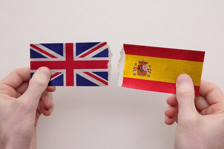 UK and Spain paper flags ripped apart. political relationship concept 写真素材