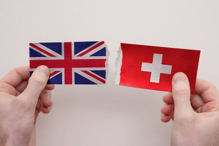 UK and Switzerland paper flags ripped apart. political relationship concept