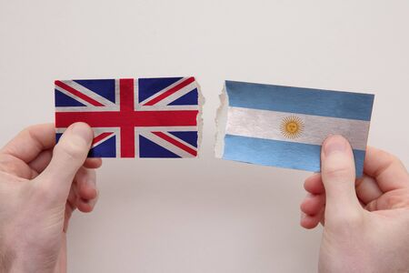 UK and Argentina paper flags ripped apart. political relationship concept Stock fotó