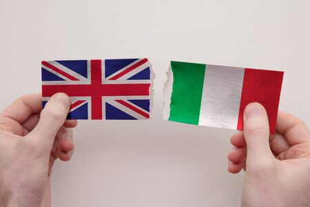 UK and Italy paper flags ripped apart. political relationship concept