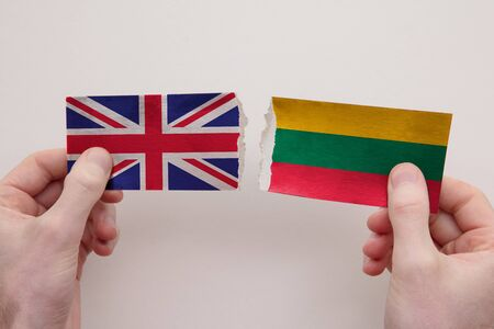 UK and Lithuania paper flags ripped apart. political relationship concept