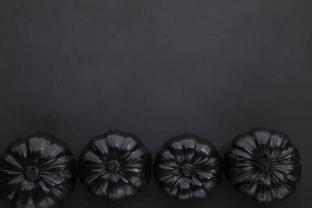 Spooky black pumpkins on a dark background. Halloween lay flat background