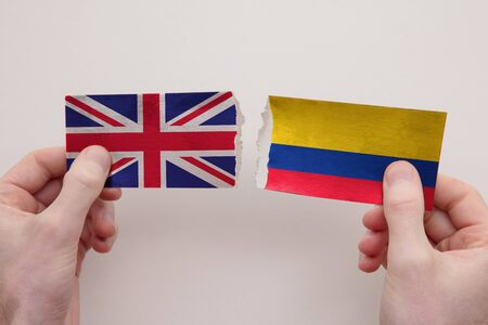 UK and Colombia paper flags ripped apart. political relationship concept