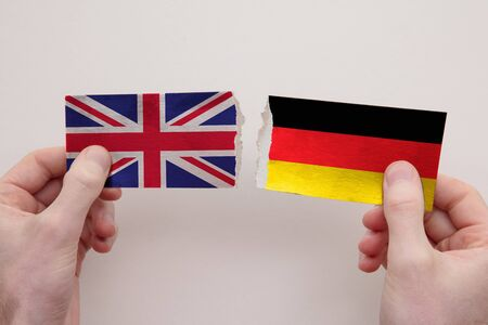 UK and Germany paper flags ripped apart. political relationship concept