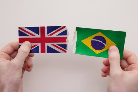 UK and Brazil paper flags ripped apart. political relationship concept