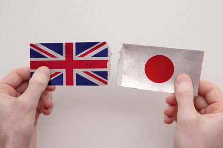 UK and Japan paper flags ripped apart. political relationship concept