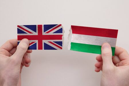 UK and Hungary paper flags ripped apart. political relationship concept