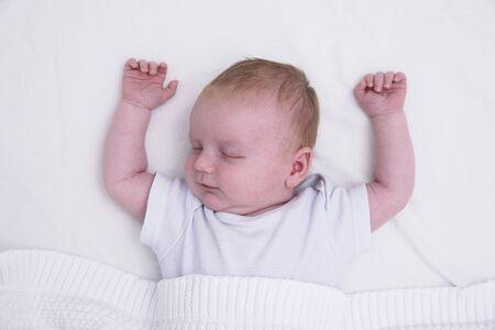 Ein schlafendes junges Baby mit erhobenen Armen. Süßes Baby schläft