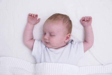 A sleeping young baby with their arms up. Cute baby asleep