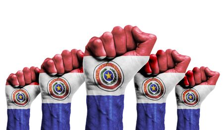 A raised fist of a protesters painted with the Paraguay flag Foto de archivo