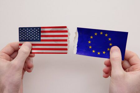 USA and European Union paper flags ripped apart. political relationship concept