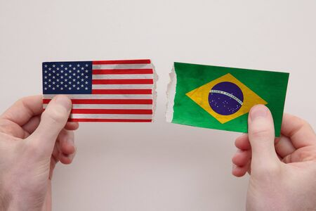 USA and Brazil paper flags ripped apart. political relationship concept