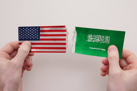 USA and Saudi Arabia paper flags ripped apart. political relationship concept 写真素材