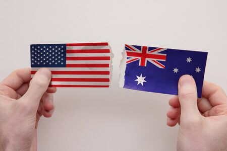USA and Australia paper flags ripped apart. political relationship concept
