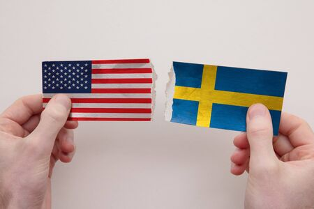 USA and Sweden paper flags ripped apart. political relationship concept