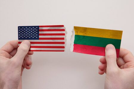 USA and Lithuania paper flags ripped apart. political relationship concept