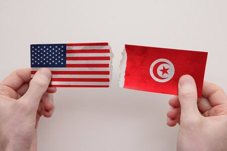 USA and Tunisia paper flags ripped apart. political relationship concept