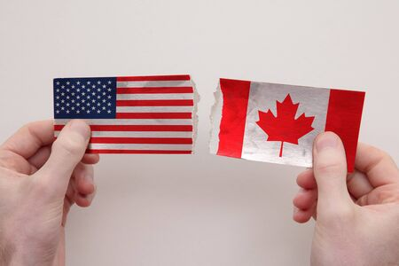 USA and Canada paper flags ripped apart. political relationship concept