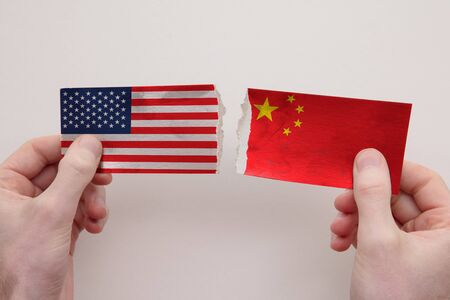 USA and China paper flags ripped apart. political relationship concept