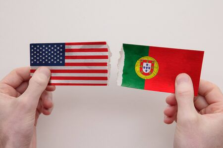 USA and Portugal paper flags ripped apart. political relationship concept