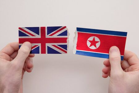 UK and North Korea paper flags ripped apart. political relationship concept 写真素材