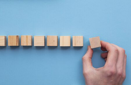 Hand choosing a wooden block from a set. Business choice concept