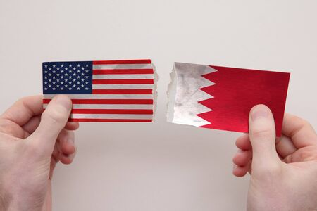 USA and Bahrain paper flags ripped apart. political relationship concept