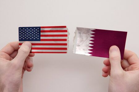 USA and Qatar paper flags ripped apart. political relationship concept