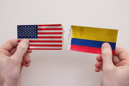 USA and Colombia paper flags ripped apart. political relationship concept