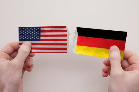 USA and Germany paper flags ripped apart. political relationship concept