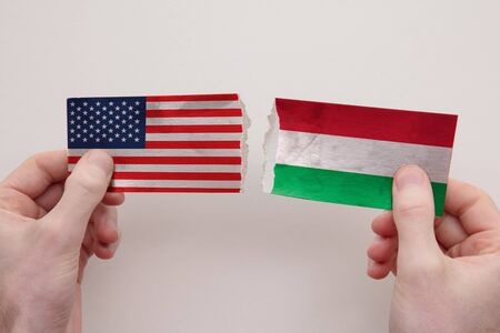 USA and Hungary paper flags ripped apart. political relationship concept