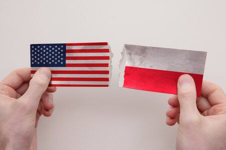 USA and Poland paper flags ripped apart. political relationship concept
