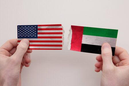 USA and UAE paper flags ripped apart. political relationship concept