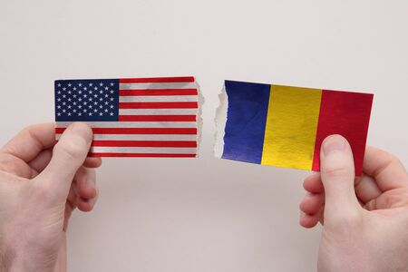 USA and Romania paper flags ripped apart. political relationship concept